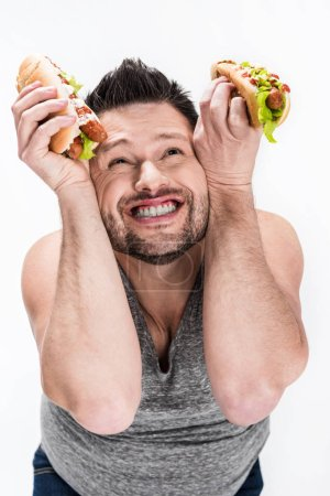 Photo for Happy overweight man holding hot dogs isolated on white - Royalty Free Image
