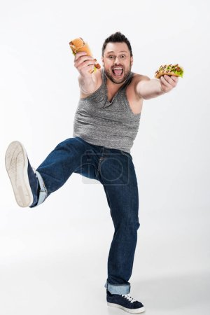 Photo for Excited overweight man holding hot dogs and looking at camera on white - Royalty Free Image