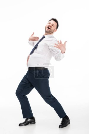 Photo for Excited overweight man in tight formal wear gesturing with hands on white - Royalty Free Image
