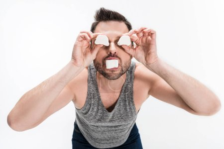 Photo pour Chubby man in grey tank top holding marshmallows in front of face isolated on white - image libre de droit