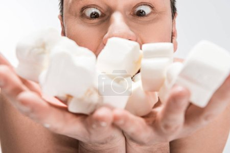 Photo for Selective focus of excited man holding marshmallows isolated on white - Royalty Free Image