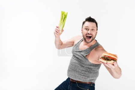 Photo for Excited overweight man holding celery and burger isolated on white with copy space - Royalty Free Image