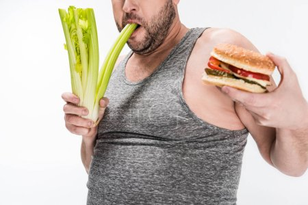 Photo for Cropped view of overweight man biting celery while holding burger isolated on white - Royalty Free Image