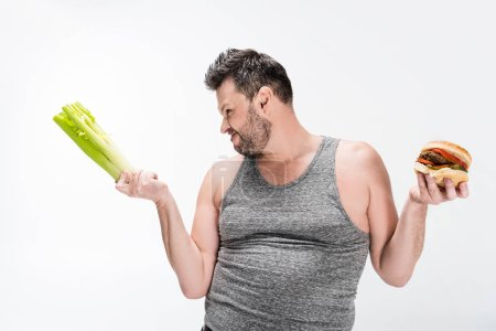 Photo for Skeptical overweight man holding celery and burger isolated on white - Royalty Free Image