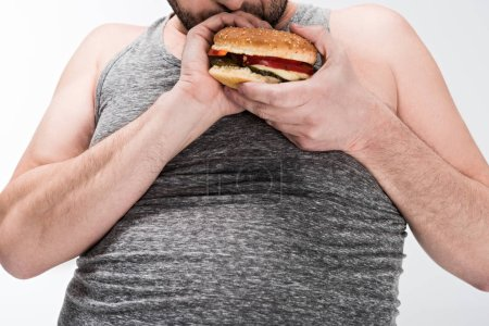 Photo for Cropped view of overweight man holding delicious burger isolated on white - Royalty Free Image