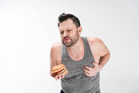 Photo for Overweight man holding burger and touching chest on white with copy space - Royalty Free Image