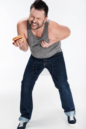 Photo for Overweight man in tank top holding burger and touching chest on white - Royalty Free Image