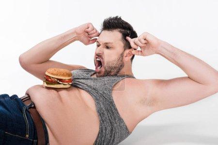 Photo pour Hurler homme en surpoids avec hamburger sur le ventre couché et faire de l'exercice abdominal sur blanc - image libre de droit