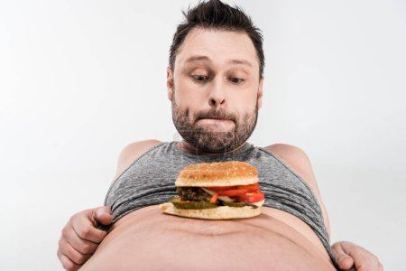 Photo for Overweight man looking at burger on belly isolated on white - Royalty Free Image