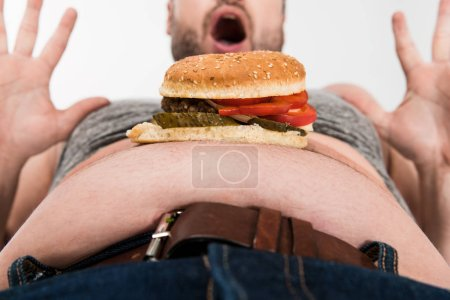 partial view of excited overweight man with burger on belly gesturing isolated on white