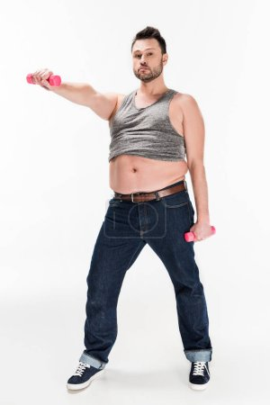 Photo for Overweight man looking at camera while working out with pink dumbbells on white - Royalty Free Image