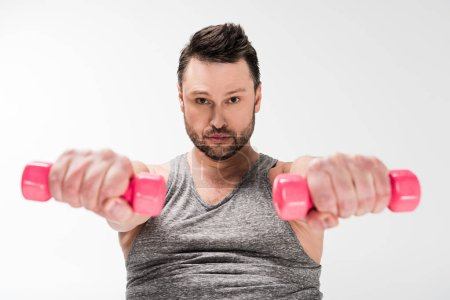 Photo for Overweight man looking at camera while working out with pink dumbbells isolated on white - Royalty Free Image