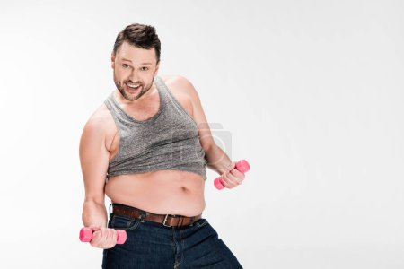 Photo for Happy overweight man looking at camera while working out with pink dumbbells isolated on white with copy space - Royalty Free Image