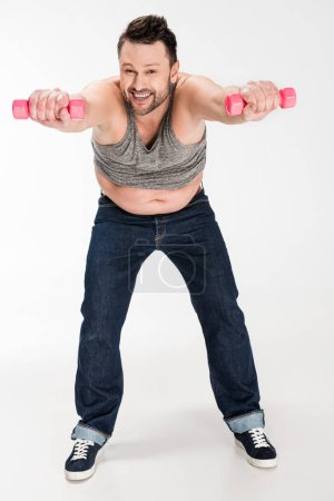 Photo for Happy overweight man looking at camera while working out with pink dumbbells on white - Royalty Free Image