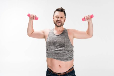 Photo for Smiling overweight man looking at camera while working out with pink dumbbells isolated on white - Royalty Free Image