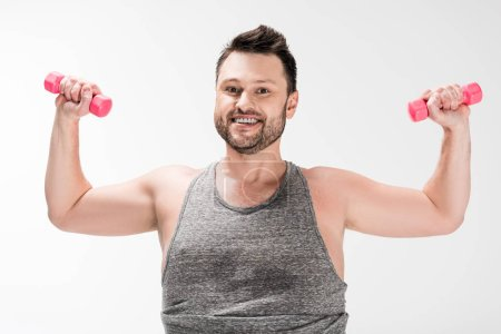 Foto de Smiling overweight man looking at camera while working out with pink dumbbells isolated on white - Imagen libre de derechos