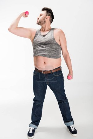 Photo for Overweight man in tank top working out with pink dumbbells on white - Royalty Free Image