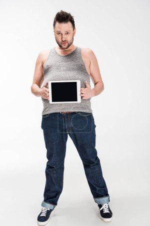 Photo pour Homme en surpoids regardant l'appareil-photo et affichant la tablette numérique avec l'écran blanc sur le blanc - image libre de droit