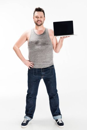 Photo for Happy overweight man looking at camera and showing laptop with blank screen isolated on white - Royalty Free Image
