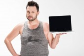 """Постер, картина, фотообои """"overweight man looking at camera and showing laptop with blank screen isolated on white"""""""