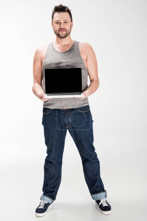 Photo pour Overweight man looking at camera and showing laptop with blank screen isolated on white - image libre de droit