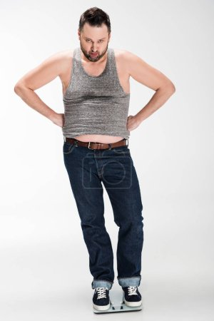 Photo for Angry overweight man with hands akimbo standing on electronic weight scales and looking at camera isolated on white - Royalty Free Image