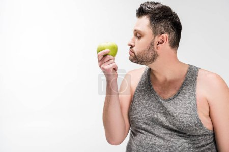 Foto de Overweight man holding green apple isolated on white with copy space - Imagen libre de derechos