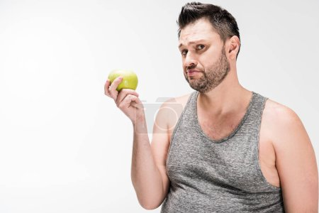 Photo for Dissatisfied overweight man holding green apple and looking at camera isolated on white - Royalty Free Image