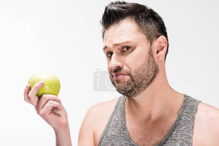 Photo for Dissatisfied chubby man holding green apple and looking at camera isolated on white - Royalty Free Image