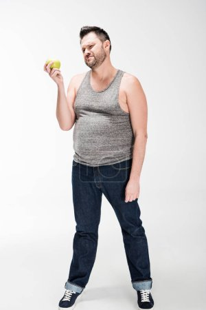 Photo for Dissatisfied overweight man in tank top holding green apple on white - Royalty Free Image