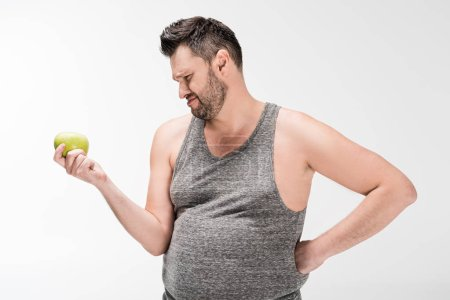 Photo for Dissatisfied overweight man holding green apple isolated on white - Royalty Free Image