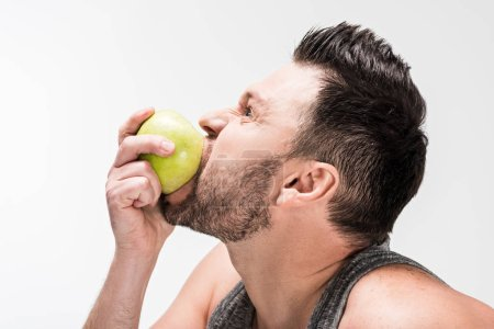 Photo for Side view of chubby man eating green apple isolated on white - Royalty Free Image