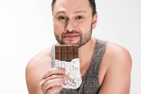 Photo for Chubby man looking at camera and holding chocolate isolated on white - Royalty Free Image
