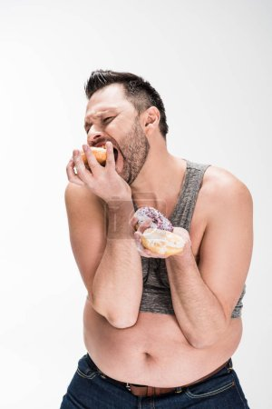Photo for Hungry overweight man eating donuts isolated on white - Royalty Free Image