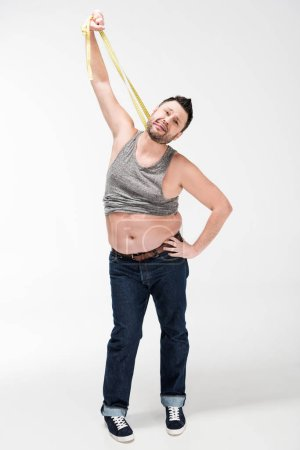 Photo for Overweight man sticking tongue out and holding measuring tape on white - Royalty Free Image