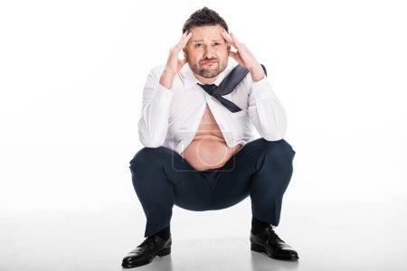 Photo pour Un homme inquiet et en surpoids en uniforme serré, les mains sur la tête, assis sur le blanc - image libre de droit