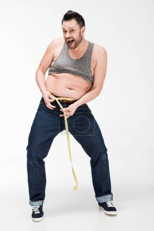 Photo for Excited overweight man looking at camera and measuring waistline with tape on white - Royalty Free Image