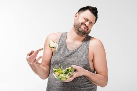 Photo for Displeased overweight man holding bowl of salad and making face expression isolated on white - Royalty Free Image