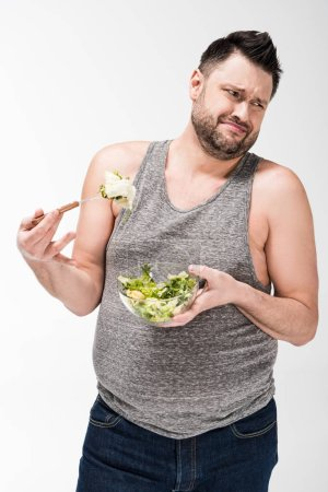 Photo for Dissatisfied overweight man holding bowl of salad isolated on white - Royalty Free Image