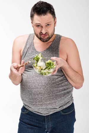 Photo for Dissatisfied overweight man holding bowl of salad on white - Royalty Free Image