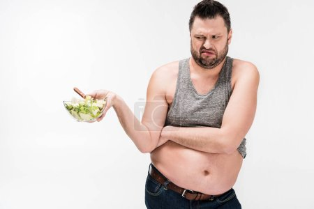 Photo for Overweight man holding bowl of salad in disgust isolated on white - Royalty Free Image