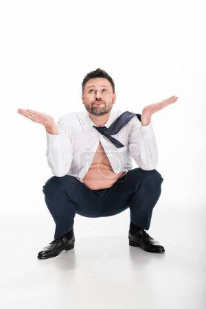Photo pour Homme confus en surpoids dans l'usure formelle serrée faisant le geste de haussement d'épaules tout en s'asseyant sur le blanc - image libre de droit