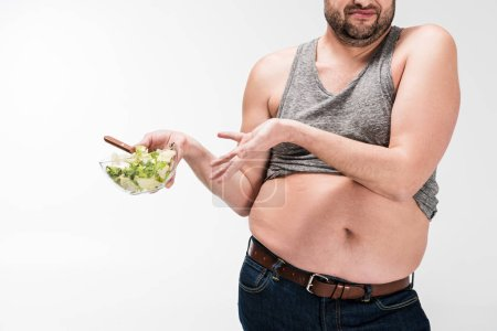 Photo for Cropped view of overweight man holding bowl of salad in disgust isolated on white - Royalty Free Image