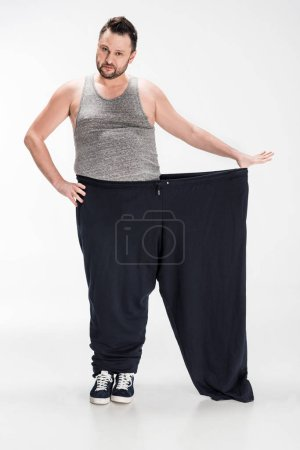 Photo for Overweight man holding oversize pants after weight loss and looking at camera on white - Royalty Free Image