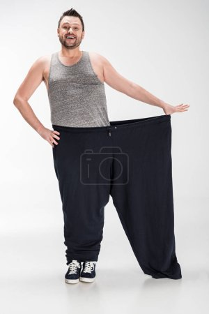 Photo for Smiling overweight man holding oversize pants after weight loss on white - Royalty Free Image