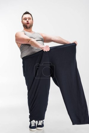Photo for Surprised overweight man holding oversize pants after weight loss on white - Royalty Free Image