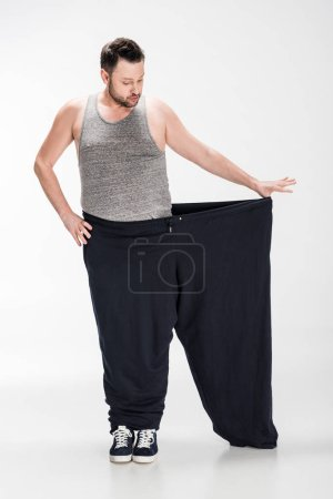 Photo for Overweight man in tank top holding oversize pants after weight loss on white - Royalty Free Image