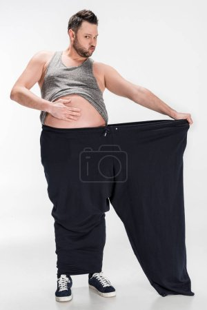 Photo for Overweight man touching belly while holding oversize pants after weight loss on white - Royalty Free Image