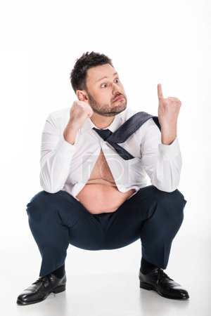 Photo for Surprised overweight man in tight formal wear looking at pinky finger while sitting on white - Royalty Free Image