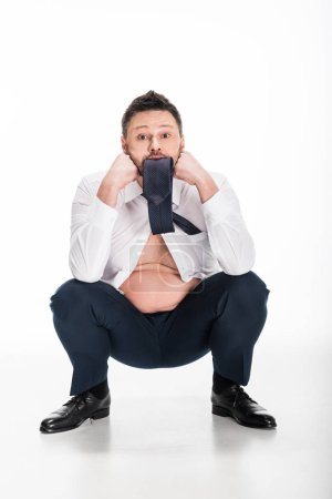 Photo for Overweight man in tight formal wear biting tie while sitting on white - Royalty Free Image